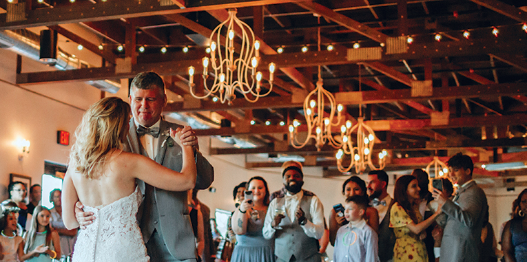 Father and daughter dancing at her wedding with onlookers watching them in a large room with exposed roof trusses