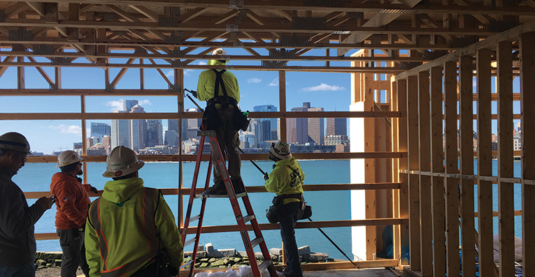 Group of construction workers in the inside of a framed building that overlooks a body of water with high rise buildings on the other side