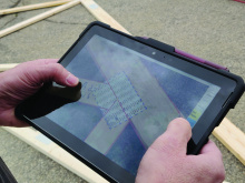 Digital QC on a tablet screen with a truss in the background.