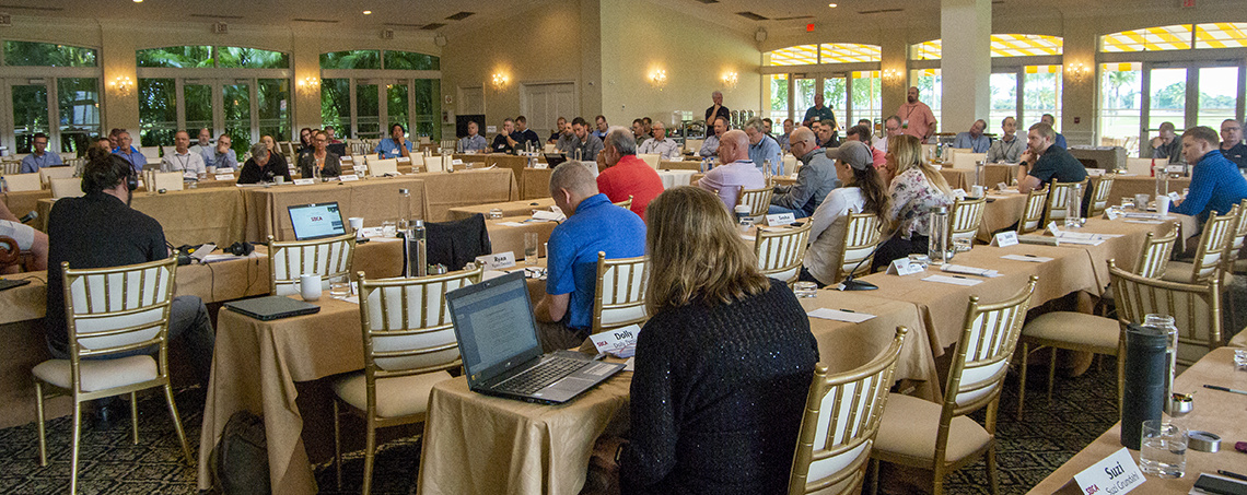 Attendees at the Miami open quarterly meeting sitting at tables during a presentation